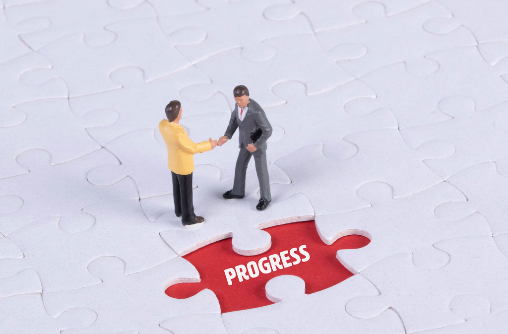Two miniature man shaking hands and a missing puzzle piece with Progress text
