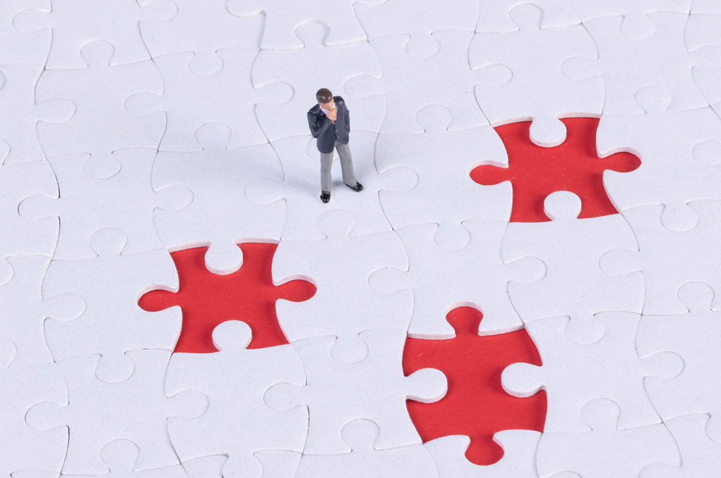 Businessman with jigsaw puzzle missing pieces