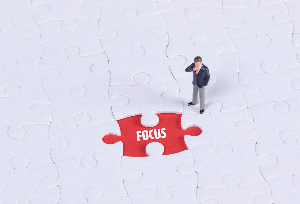 Miniature man looking at a missing puzzle piece with Focus text