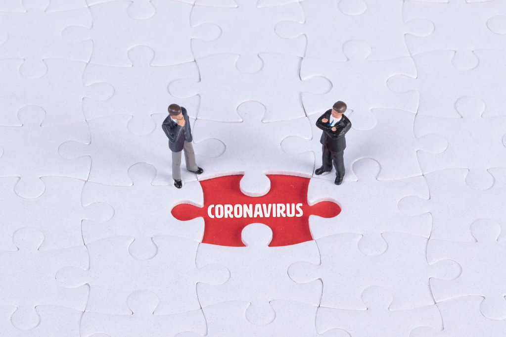 Two miniature man looking at a missing puzzle piece with Coronavirus text