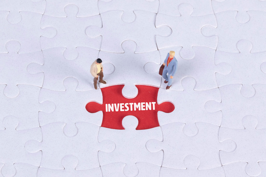 Two miniature man looking at a missing puzzle piece with Investment text