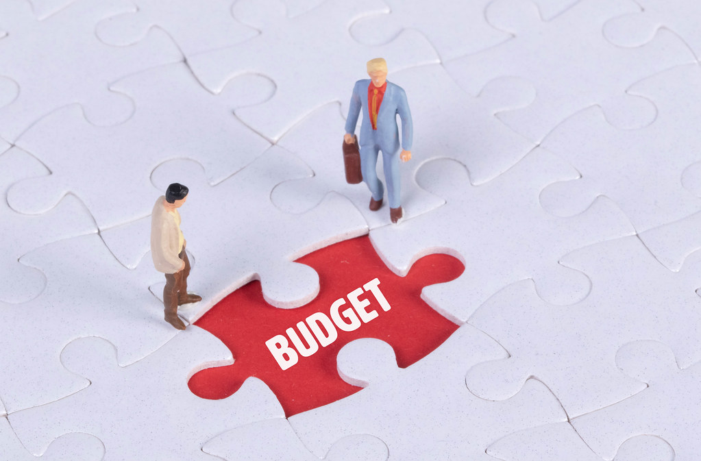 Two miniature man looking at a missing puzzle piece with Budget text