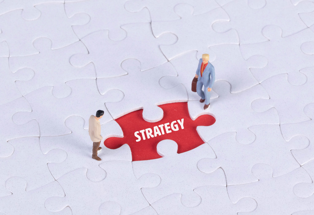 Two miniature man looking at a missing puzzle piece with Strategy text