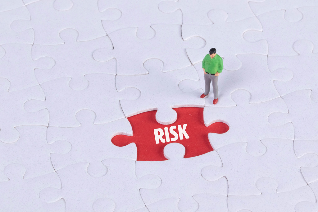 Miniature man looking at a missing puzzle piece with Risk text