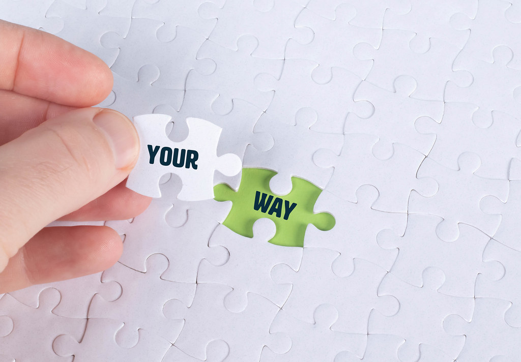 Hand holding piece of jigsaw puzzle with word your & way