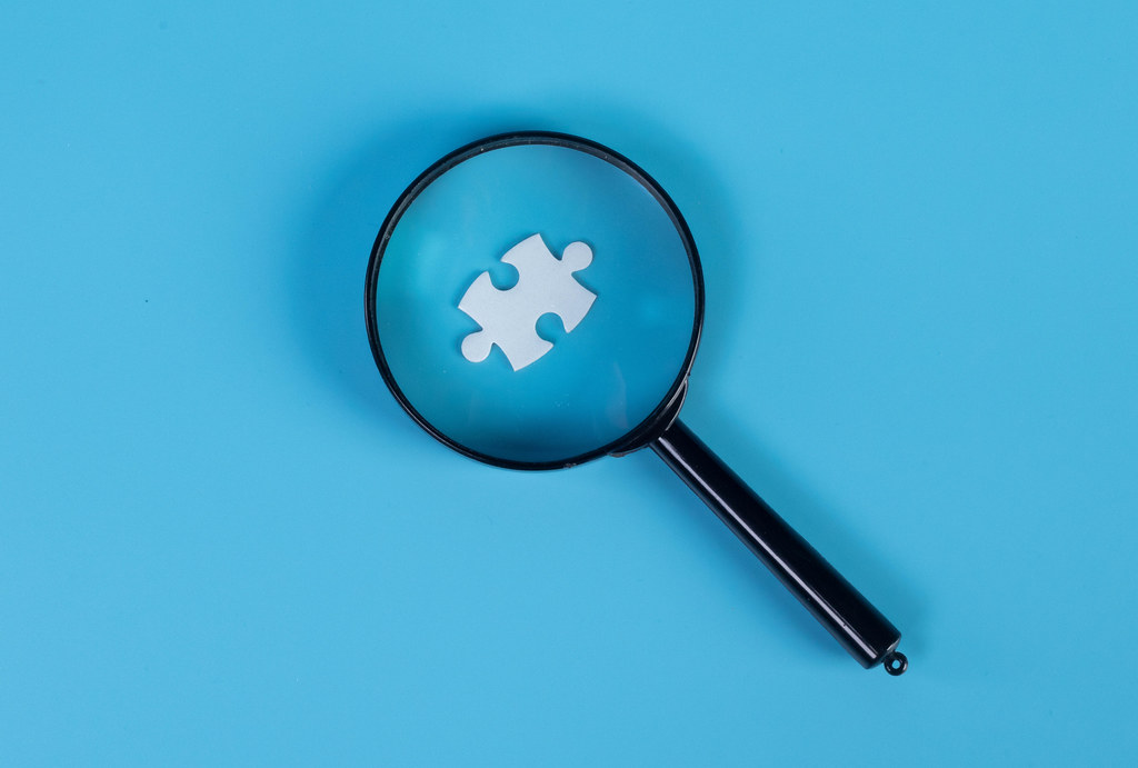 Magnifying glass and puzzle piece on blue background