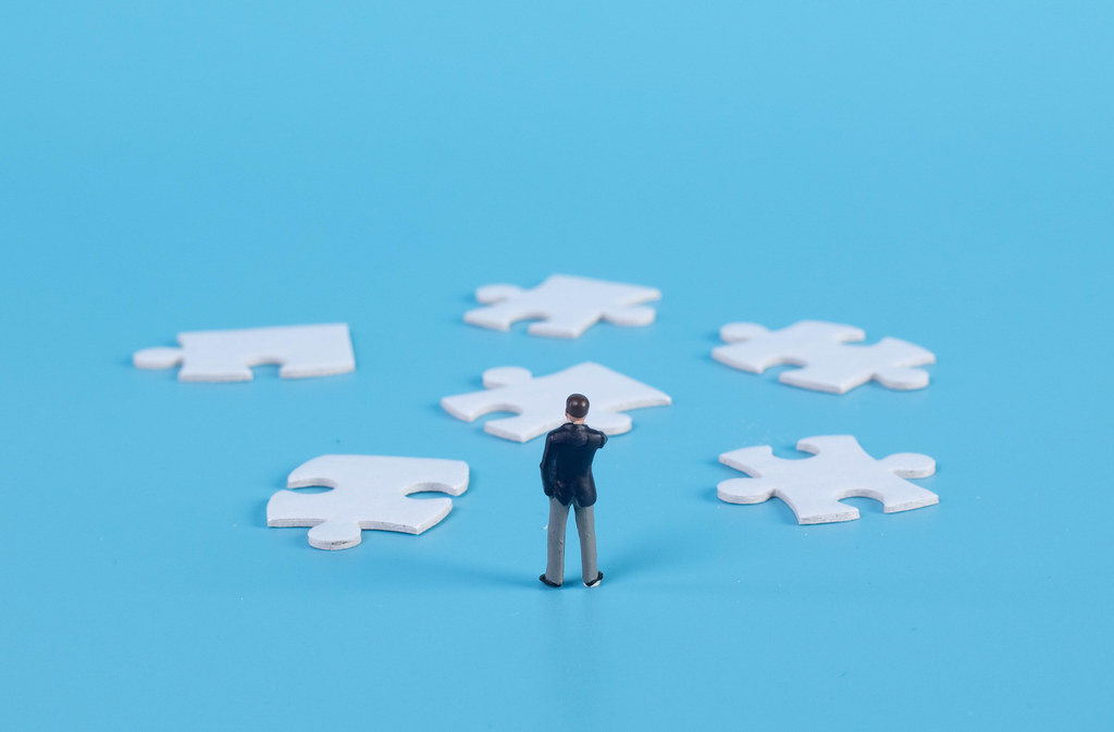 A miniature businessman standing with a puzzle pieces on blue background