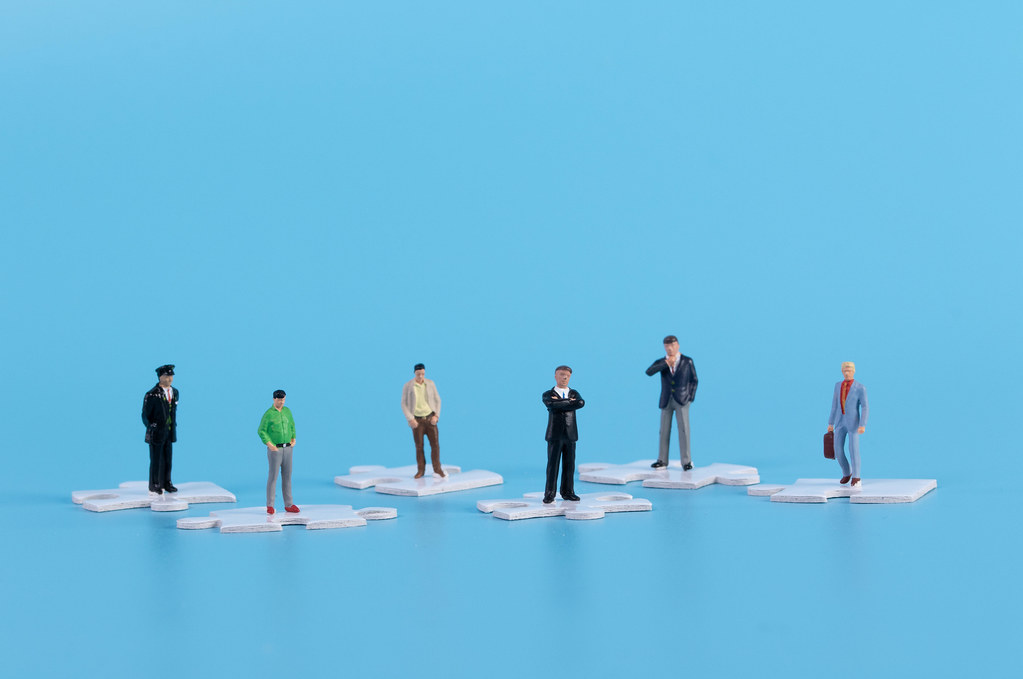 Miniature people standing on white jigsaw puzzle pieces with blue background