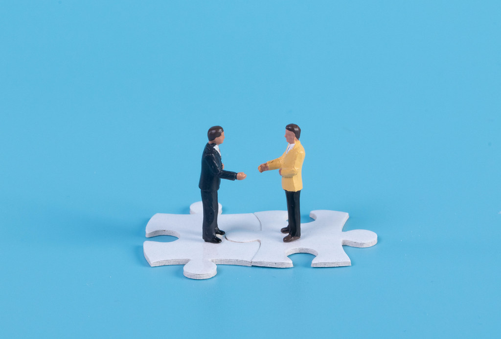 Miniature businessman handshaking on white jigsaw puzzle piece