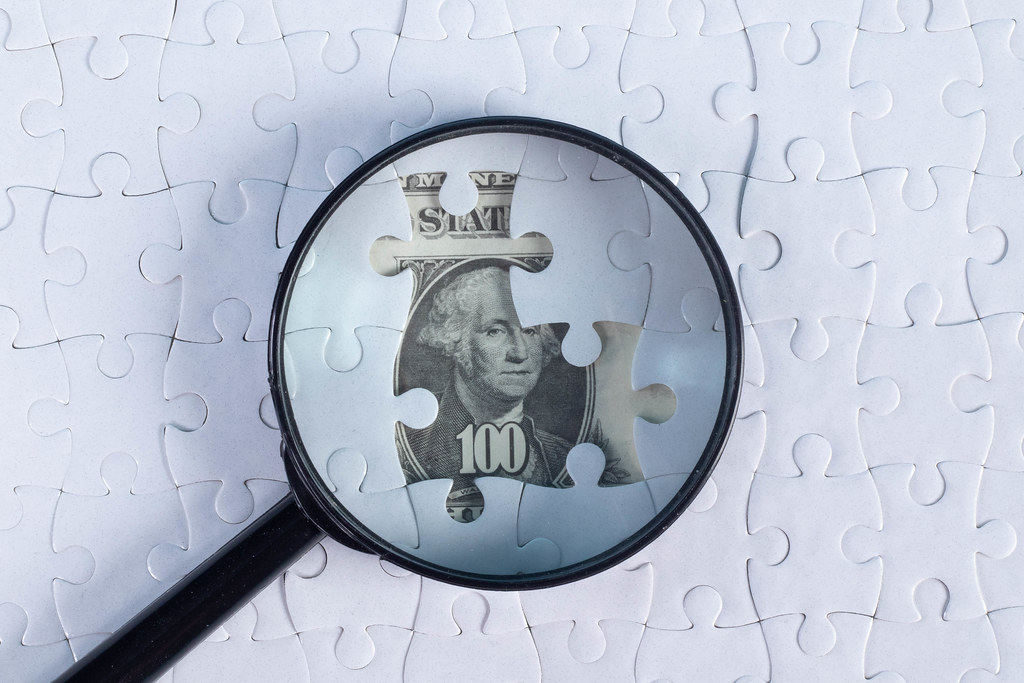Puzzle and magnifier on money