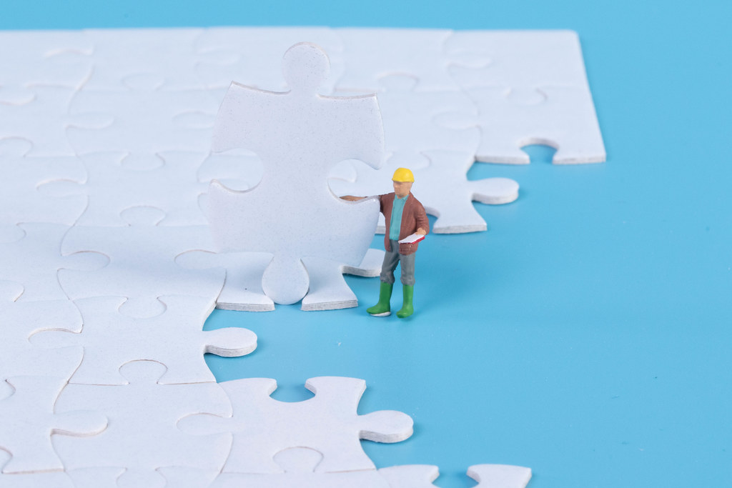 Construction worker with jigsaw puzzle pieces
