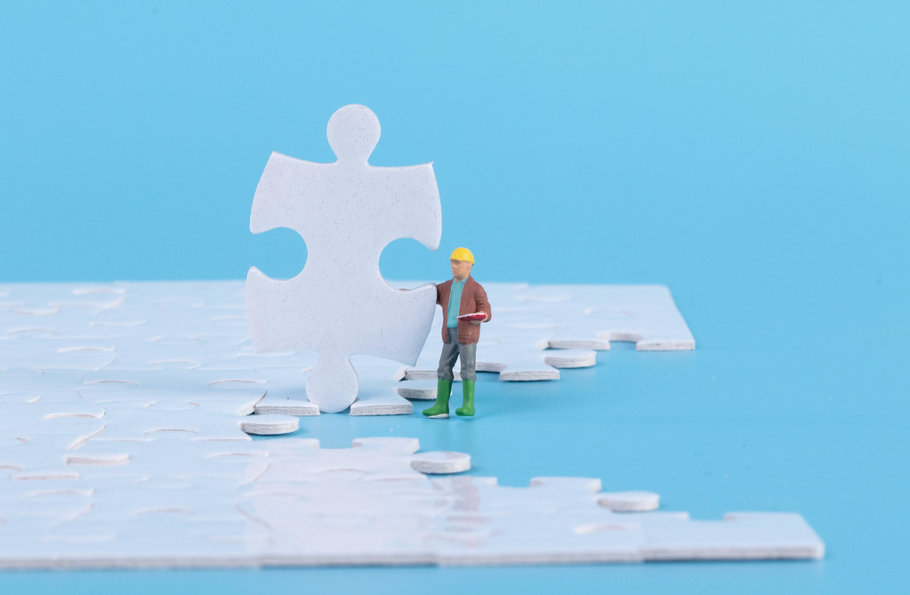 Construction worker with jigsaw puzzle pieces on blue background