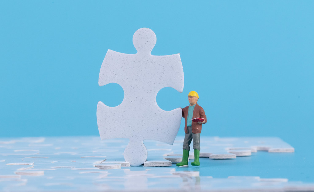 Miniature construction worker with jigsaw puzzle pieces on blue background