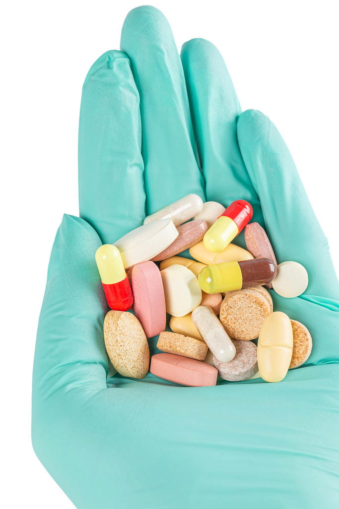 Close-up, many multi-colored tablets, pills and capsules in hand