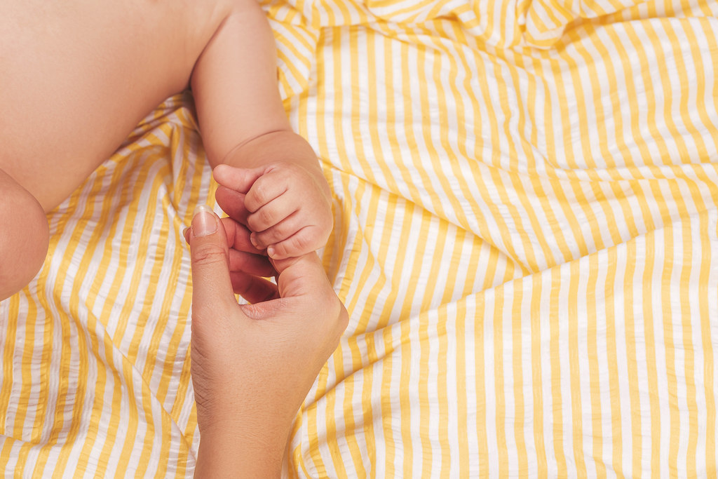 Baby's hand holding mother's forefinger