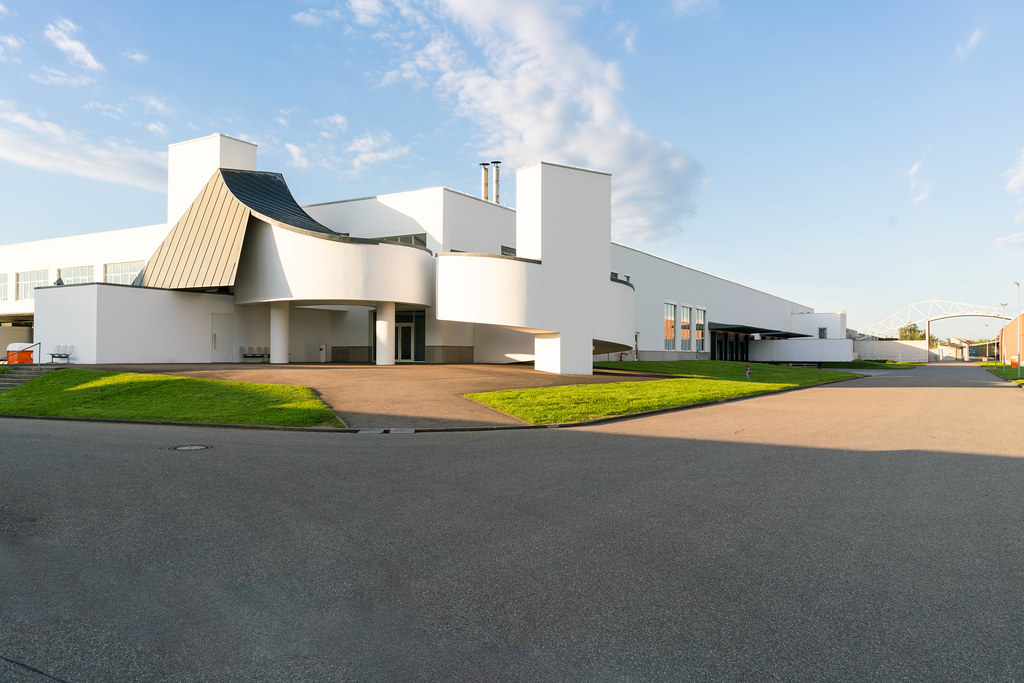 White concrete Bauhaus style factory building on Vitra museum campus by Frank Gehry