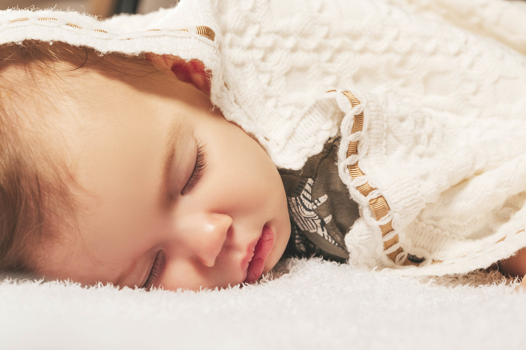 Close-up portrait of adorable baby boy sleeping in bed