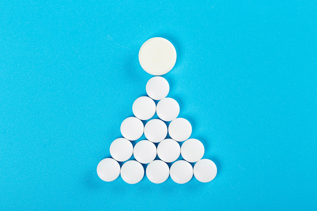 The sign or symbol of a woman is made of white tablets on a blue background