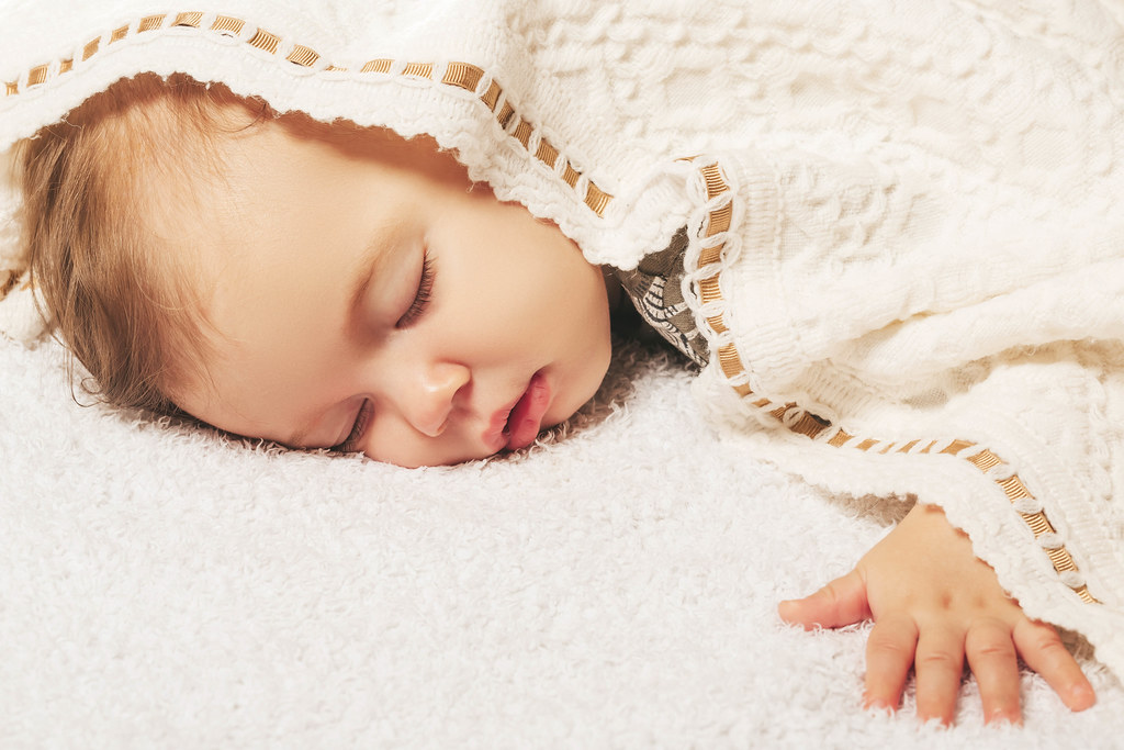 Close-up portrait of a beautiful sleeping baby on a soft bed