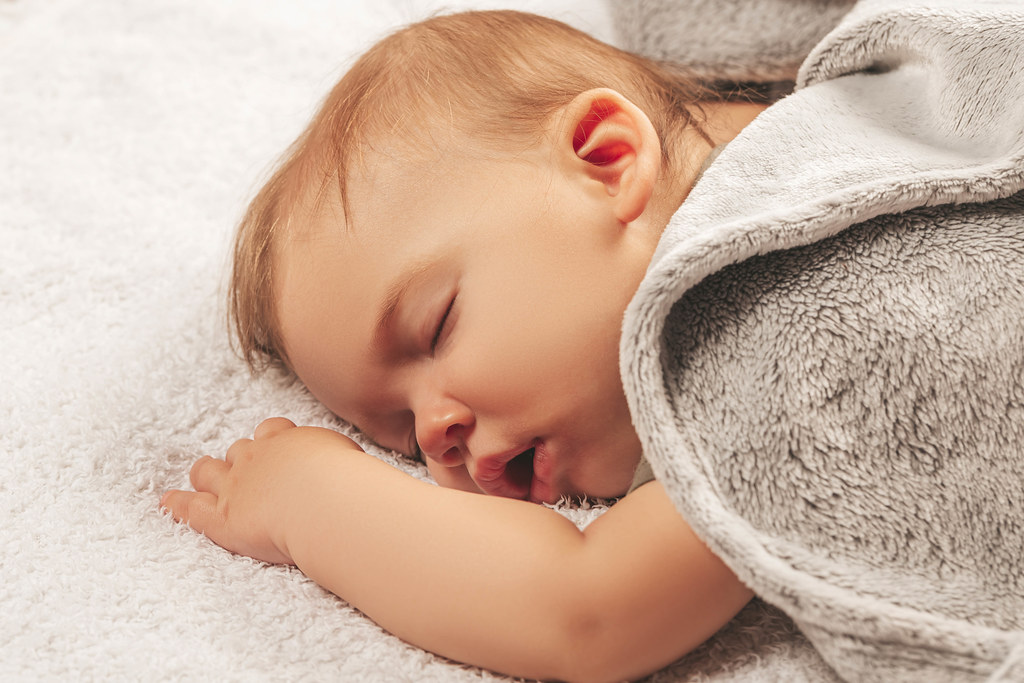 Carefree beautiful sleep of a little boy with open mouth