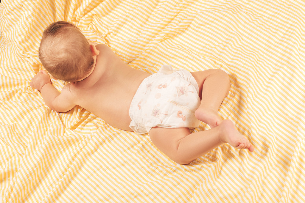 Top view, a small baby in diapers lies on his stomach