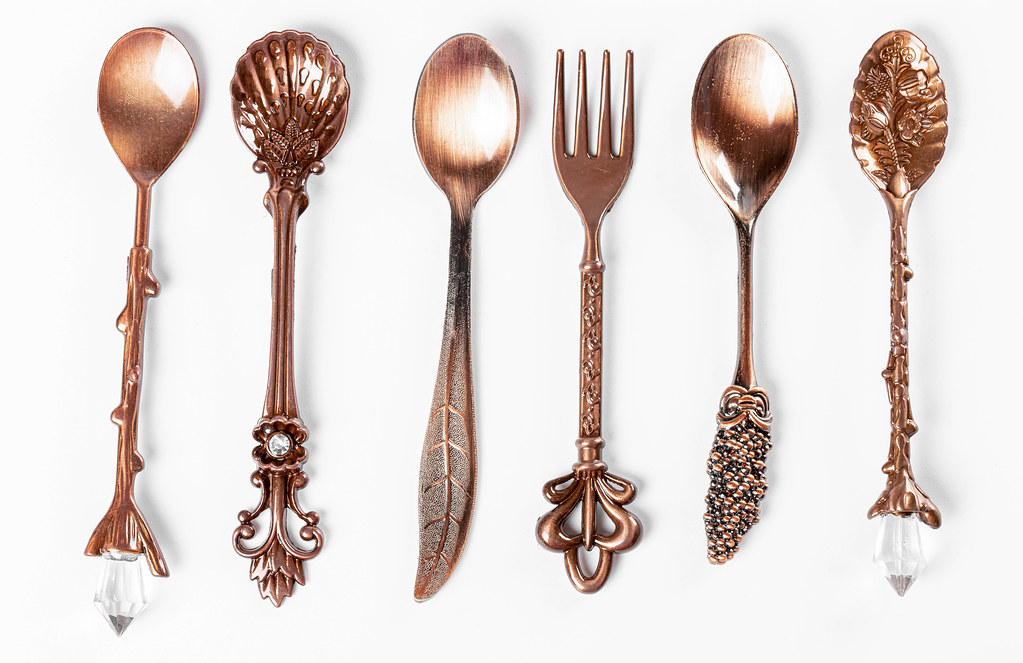 Coppers teaspoons and fork with decorated on handles ornament, top view