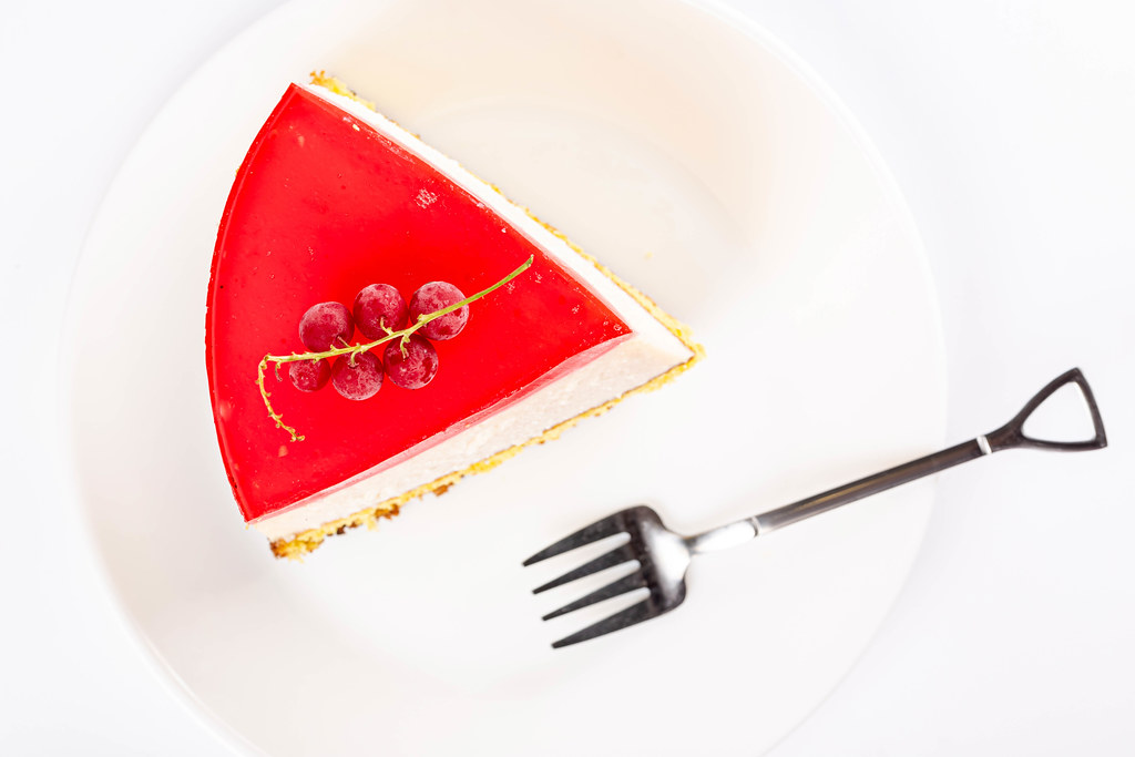 Top view, a slice of raspberry cheesecake with currant berries