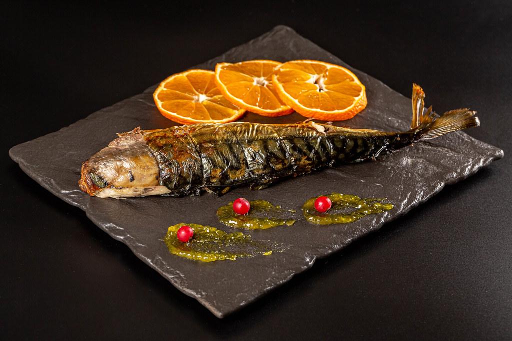 Baked mackerel on a dark background with orange