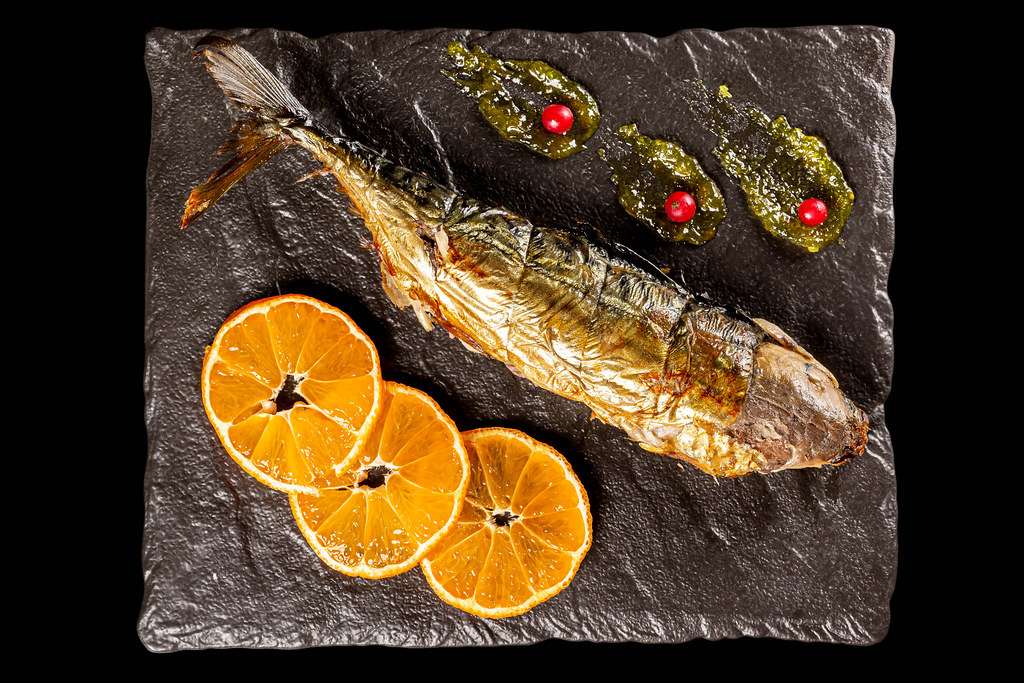 Top view, baked mackerel with orange slices and red currant berries