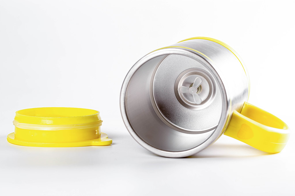 Empty metal mug mixer on white background with yellow lid