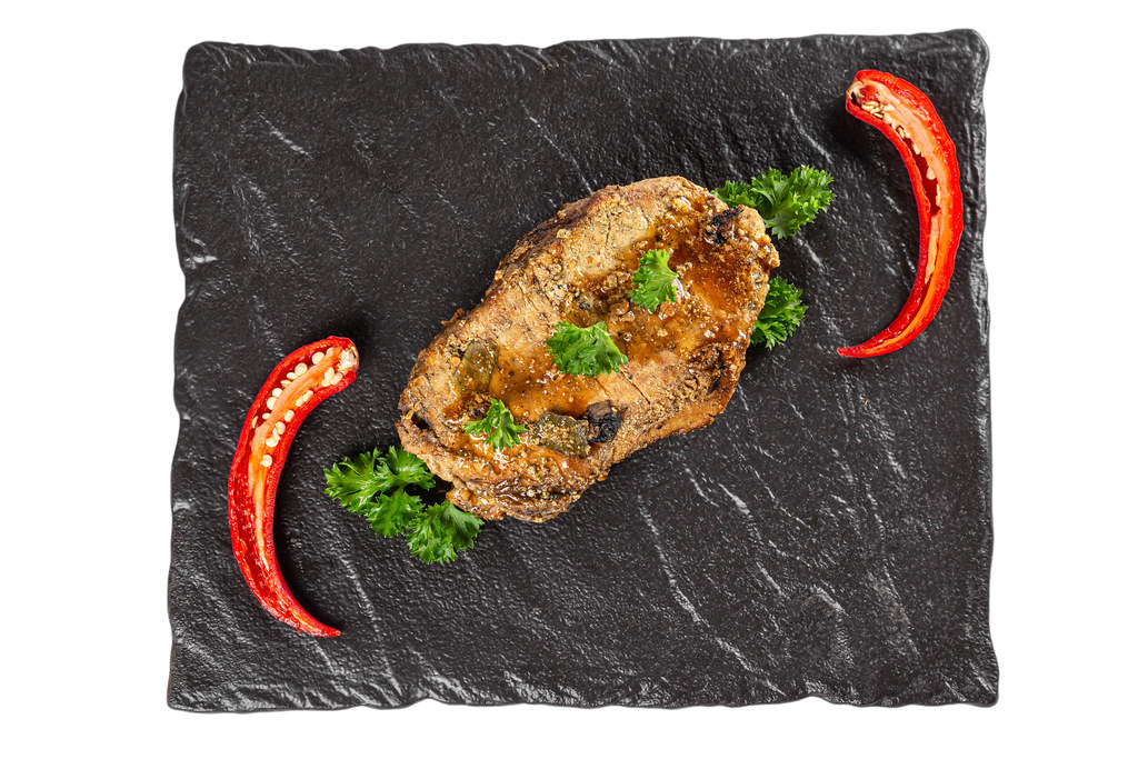 Top view, baked meat on a black stone tray
