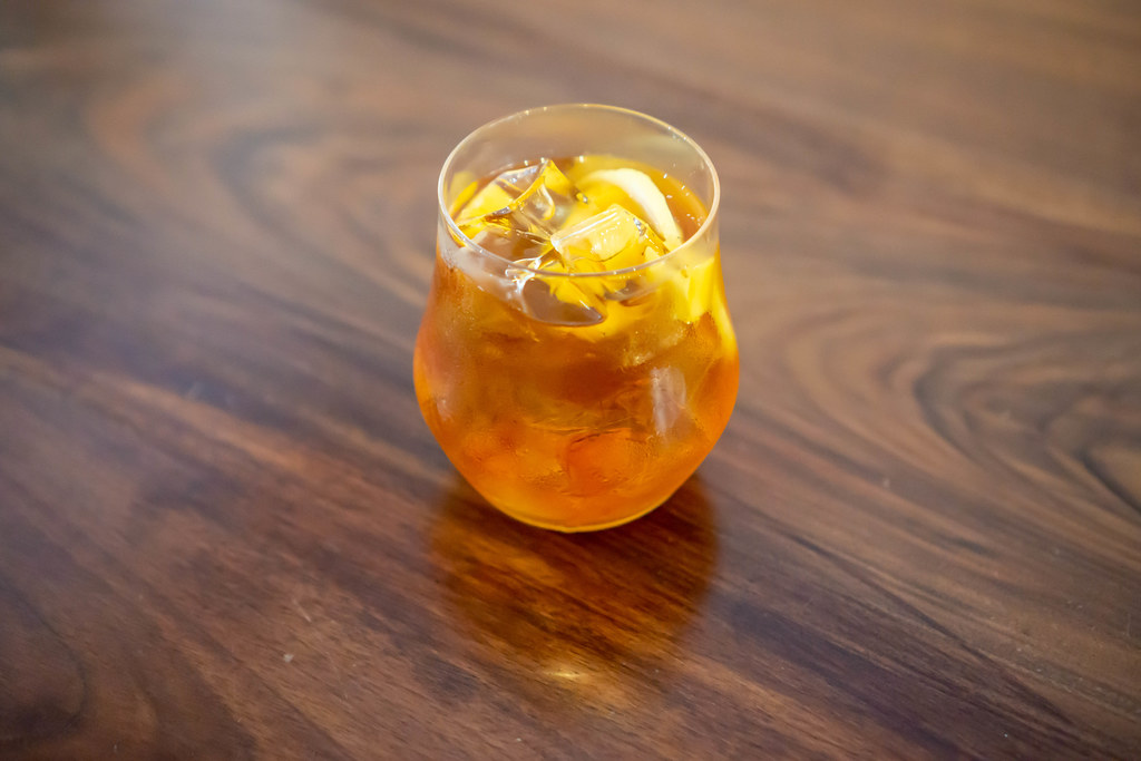 A Glass of Oolong Green Tea with Fresh Mango and Ice Cubes on a Wooden Table