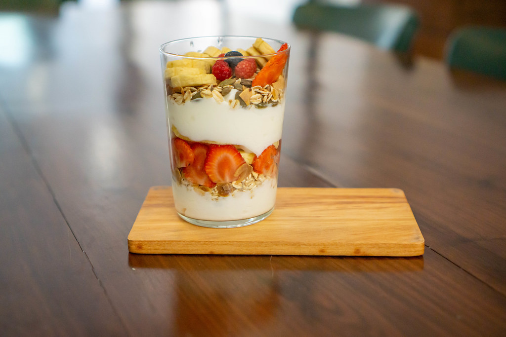 Glass of Mixed Yogurt with Cereals, Banana, Strawberries, Blueberry, Raspberry and Sunflower Seeds on a Wooden Serving Board