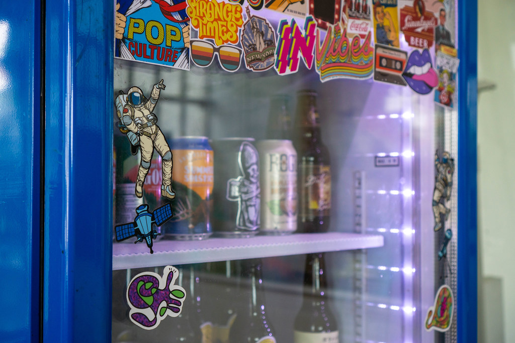 Close Up Photo of Dancing Astronaut Sticker on a Beverage Fridge with Beer Cans and Bottles inside