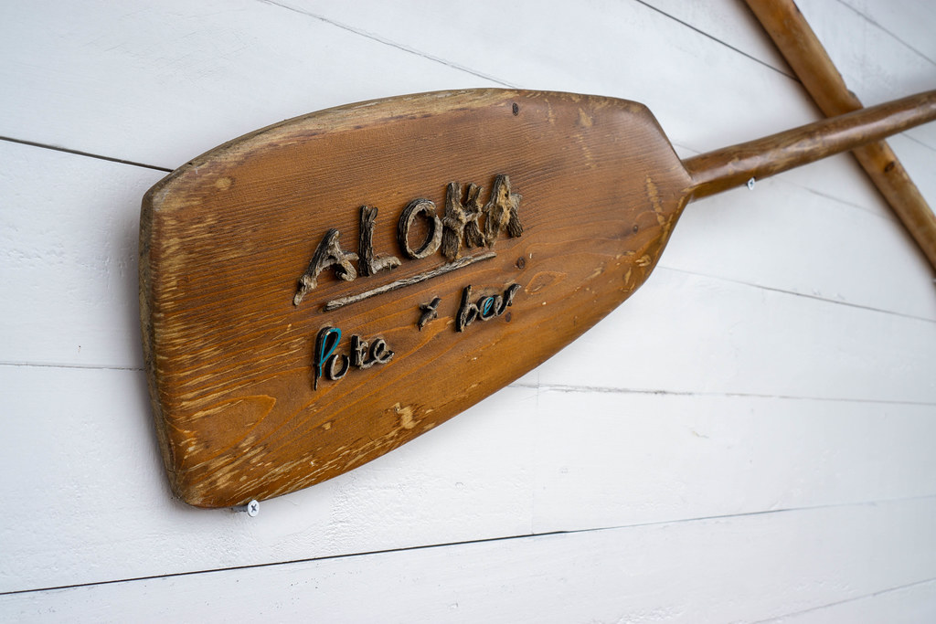 Wooden Boat Paddles attached to a Wall with Aloha Poke & Beer Restaurant Name in Ho Chi Minh City, Vietnam