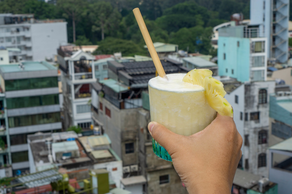 Bokeh Photo of Person holding a Virgin Pina Colada in a Cocktail Glas with Bamboo Straw and Slice of Pineapple with Buildings in the Background