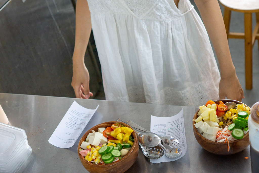 Kitchen Staff preparing Healthy Hawaiian Poke Bowls with Fresh Vegetables and Fruits with Ingredients Lists from Customers