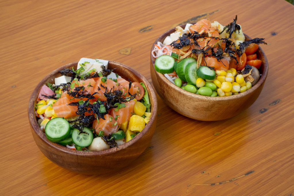 Two Healthy Poke Bowls with different fresh Vegetables, Tofu, Fried Onions, Salmon and Dried Seaweed in Wooden Bowls
