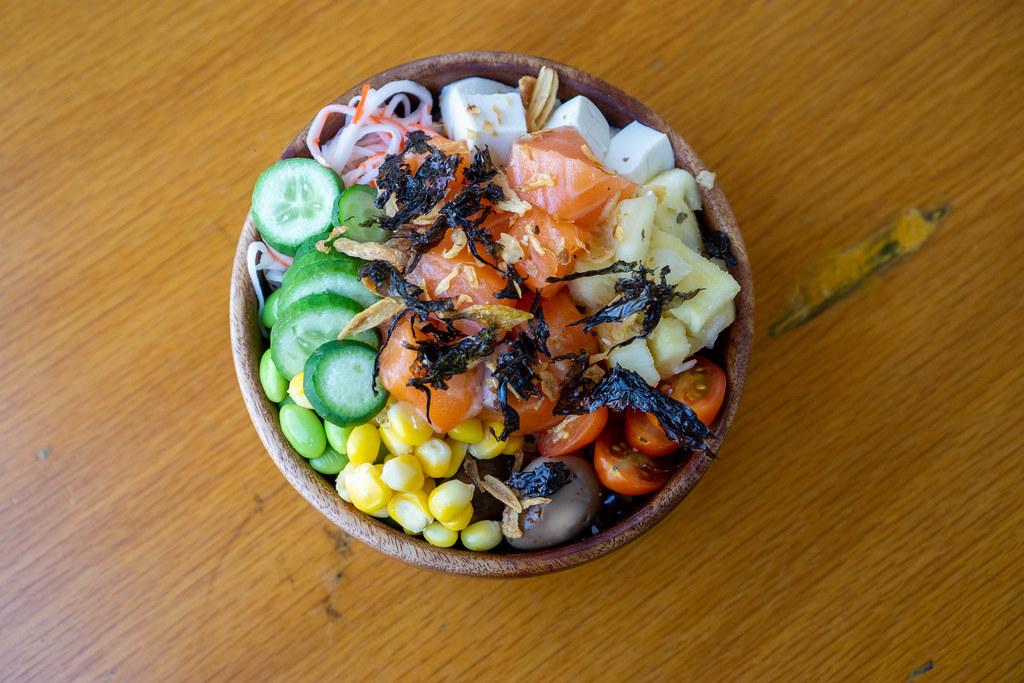 Hawaiianische Poke Bowl mit frischem Gemüse, Tofu, Wachteleier, Lachs, Röstzwiebeln und getrockneter Seetang in einer Holzschüssel Draufsicht