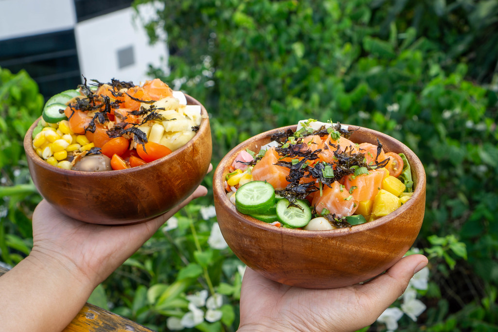 Bokeh Food Photo of Person holding two Wooden Bowls with Healthy Hawaiian Poke Dish with Plants and Flowers in the Background