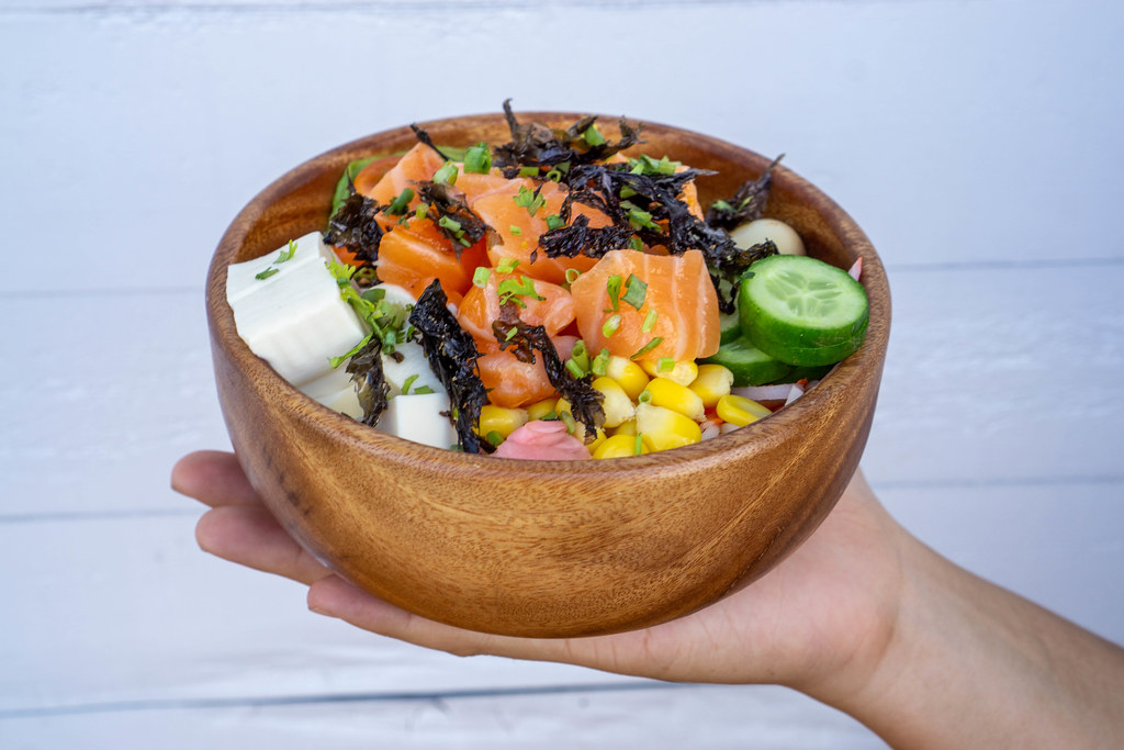 Close Up Food Photo of Person holding Hawaiian Poke Bowl with Creamy Tofu, Raw Salmon, Fresh Vegetables and topped with Dried Seaweed and Fried Onions