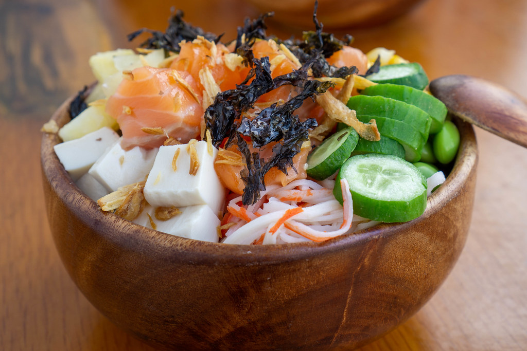 Close Up Food Photo of Wooden Bowl with Hawaiian Dish Poke Bowl with Surimi, Tofu, Fried Onions, Dried Seaweed, Vegetables and Raw Salmon