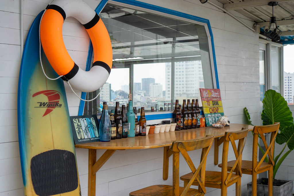 Wooden Outdoor Bar with Surfboard, Life Buoy, Beer Bottles and other Decorations at a Rooftop Restaurant in Saigon, Vietnam