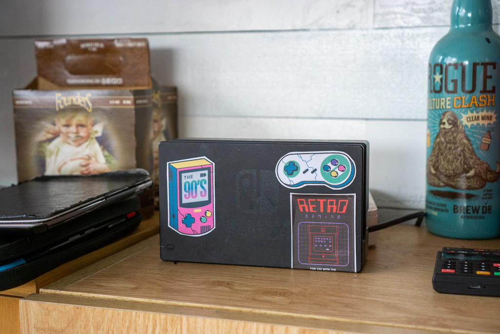 Nintendo Switch Console Dock with Retro Gaming Stickers on a Livingroom Shelf with Games and Remote Control