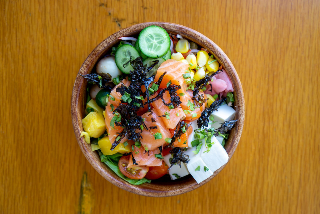 Top View Food Photo of Hawaiian Poke Bowl with fresh Vegetables, Tofu, Quail Eggs, Mango, dried Seaweed, fried Onions and Salmon in a Wooden Bowl