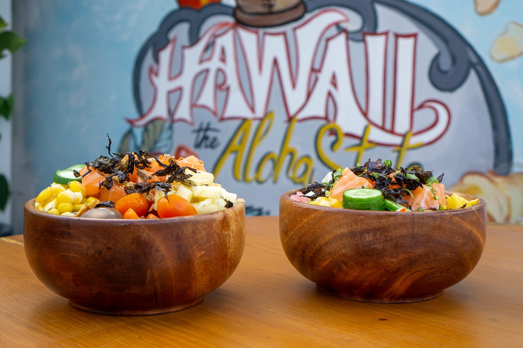 Bokeh Food Photo of two Healthy Poke Bowls with different Ingredients on a Wooden Table with Hawaii the Aloha State Drawing in the Background