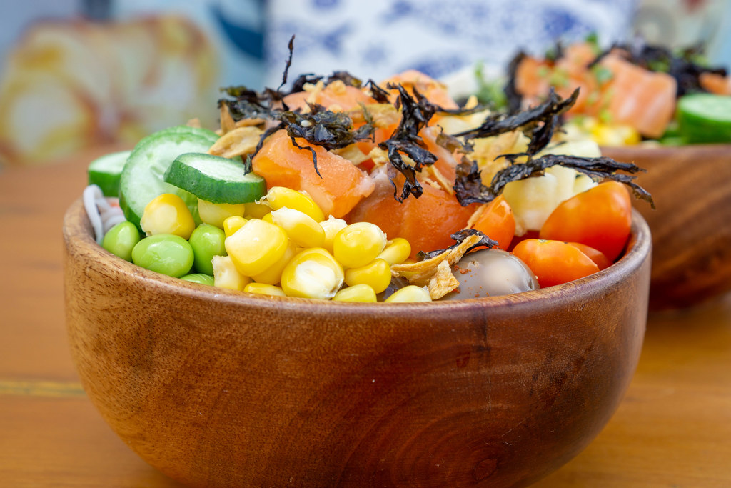 Close Up Food Photo of Hawaiian Poke Bowl with Corn, Tomatoes, Cucumber, Salmon, Fried Onions and Dried Seeweed in a Wooden Bowl
