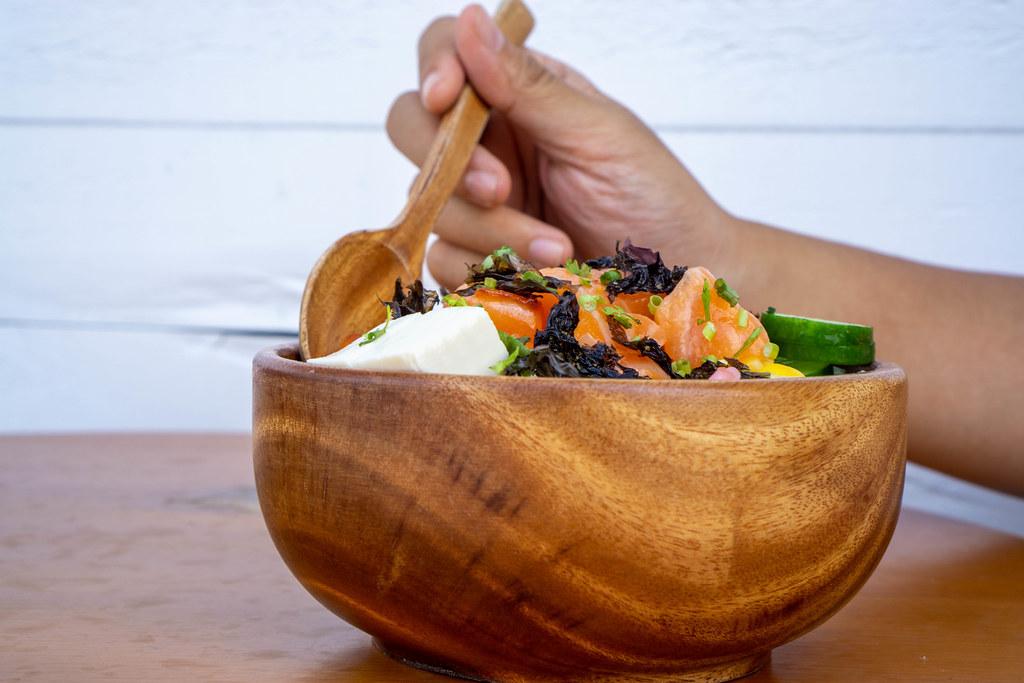 Person isst eine gesunde Hawaiianische Poke Bowl mit Tofu, rohem Lachs und Gemüse mit einem Holzlöffel Nahaufnahme