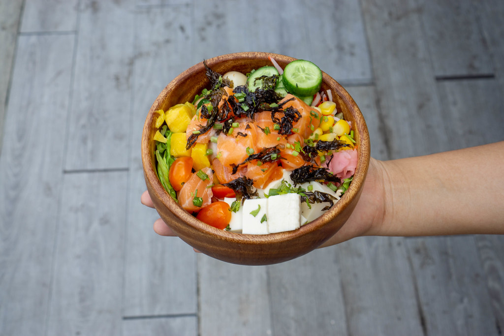 Top View Food Photo of Person holding a Wooden Bowl with Healthy Hawaiian Poke Bowl with Fresh Mango, Tofu, Vegetables and Raw Salmon