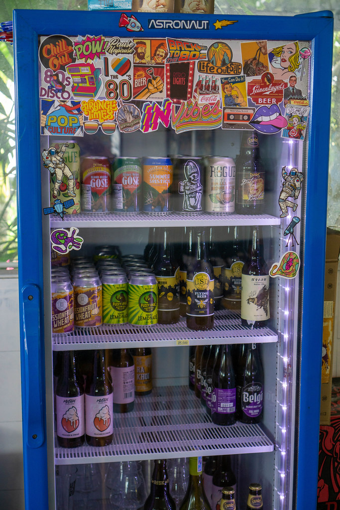 Many Retro Style Stickers on a Beverage Fridge with Beer Cans and Bottles inside it